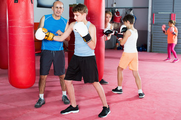 Teenage boy exercising at boxing at gym