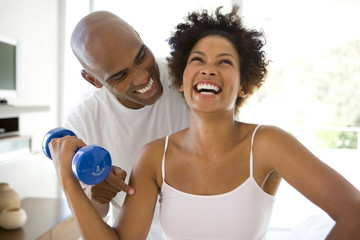 Man smiling at woman exercising with weights at home