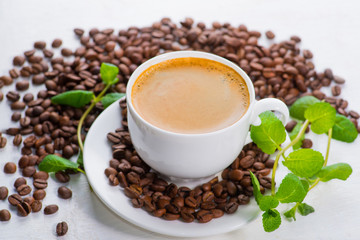 white cup of coffee on a background of scattered coffee beans on a white background