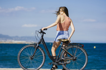 Rear view of woman with bicycle standing at beach against blue sky during sunny day