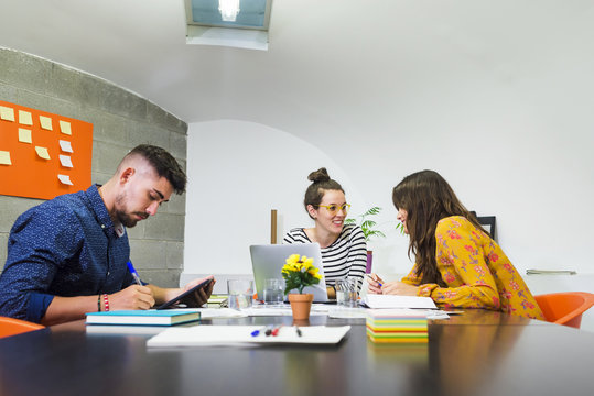 Businessman writing while female colleagues discussing at conference table in creative office
