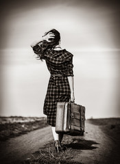Beautiful girl in plaid dress with bag on countryside. Image in black and white color style