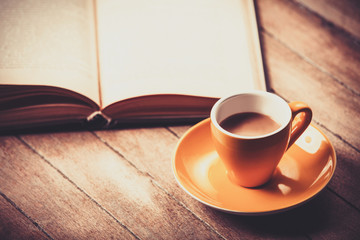 yellow cup of the coffee and vintage book. Photo with filter as a retro color image style.