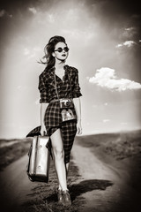 Beautiful girl in plaid dress with bag and retro camera on countryside. Image in black and white color style