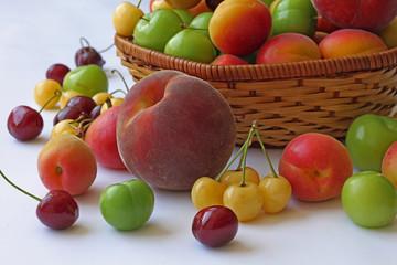 Sepet içerisinde ve beyaz zemin üzerinde çeşitli meyveler