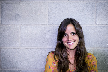 Portrait of smiling businesswoman standing against wall in office