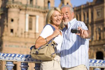 Senior couple on city break vacation taking selfie with camera