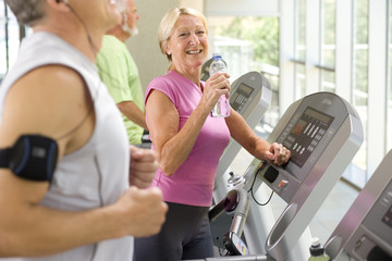Active mature woman exercising in gym on treadmill at camera
