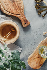 Modern kitchen metal and wooden utensils on a table for cooking. Golden spoons, bowls and cutting boards. Copy space, top view.