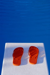 Orange Flip Flops On A Diving Board And Swimming Pool