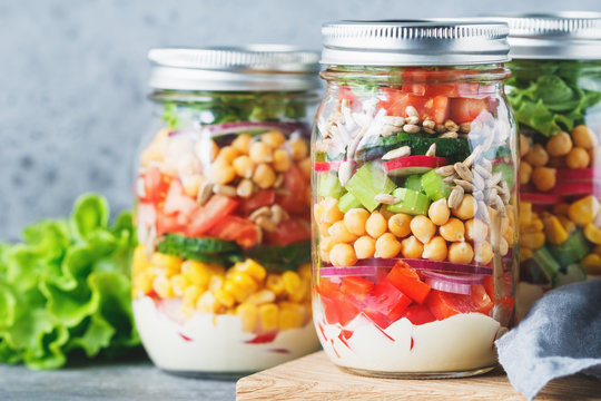 Three glass jars with layering various vegan salads for healthy lunch. The concept of fitness and vegetarian food.