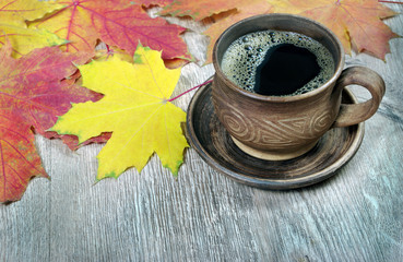 cup of coffee and yellow maple leaves on a wooden table