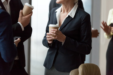 Close up of diverse work employees having casual talk enjoying coffee to go during office break, colleagues chat drinking from takeaway paper cups, workers discuss project at company meeting
