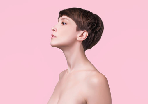Beautiful woman. Female face close up. Portrait of young caucasian woman at studio isolated on pink. Fresh skin and beauty concept. Short haircut, long neck, perfect skin