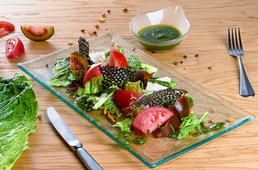 Vegetable salad with fresh tomatoes, feta, lettuce and arugula. Fresh salad on glass plate on wooden table.