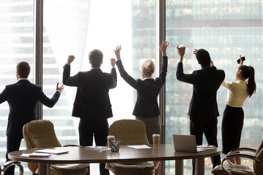 Excited office employees stand near big windows arms wide open, motivated colleagues rise hands up ready for new successful deals close or business agreement sign, workers celebrate team success