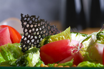 Closeup view of vegetable salad with fresh tomatoes, lettuce and arugula. Healthy food.