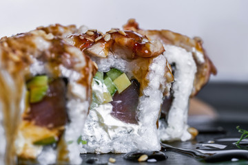 Delicious sushi roll with fish and cocumber. Sushi rolls on a black board decorated with sesame seeds and spicy sauces.