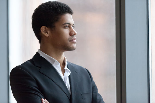 Thoughtful African American millennial employee looking in distance thinking of future career opportunities, serious black businessman dreaming of achievements or success. Concept of business vision