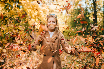 Young business fashionable dressed woman playing in park. Autumn fun. Beautiful blonde happy cheerful girl in coat throwing up maple leaves outdoor. Cute adult female enjoying like child in fall wood.