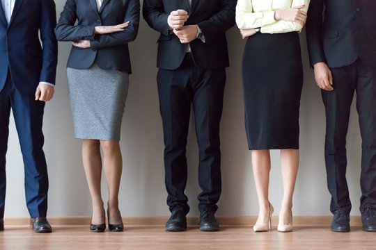 Legs of diverse work team pose for corporate photoshoot or make picture, job applicants in suits standing in row, waiting for recruiting talk or interview results. HR, hiring, employment concept