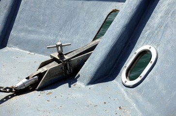 Close up of the anchor mechanism of a small passenger ferry boat, in blue grey