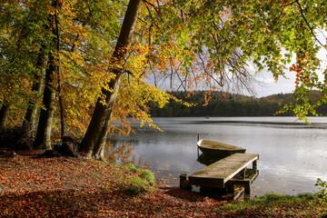 romantischer Steg mit Boot am See im Herbst