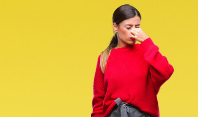 Young beautiful business woman wearing winter sweater over isolated background smelling something stinky and disgusting, intolerable smell, holding breath with fingers on nose. Bad smells concept.