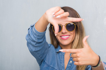 Young adult woman over grunge grey wall wearing retro sunglasses smiling making frame with hands and fingers with happy face. Creativity and photography concept.