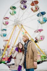 Young couple in love with a happy young man with a beard and a woman on a background of a fucking colossus, a Ferris wheel resting, a date in an amusement park in the winter in the Christmas holidays