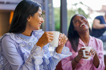 Smiling female friends at coffee shop