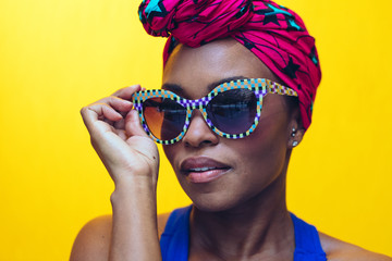 Close up of a woman with sunglasses against yellow background