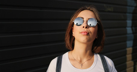 Portrait of stylish serious girl with glasses posing in city.