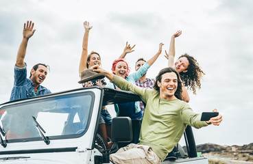 Group of happy friends taking selfie with mobile smart phone on jeep car - Young people having fun making photo during their road trip - Friendship, vacation, youth holidays lifestyle concept