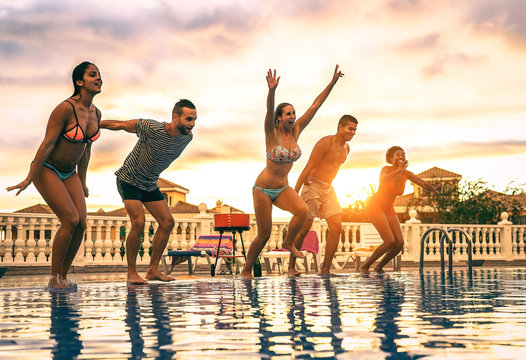 Group of happy friends jumping in the pool at sunset - Young people having fun making party in exclusive resort tropical in vacation - Concept of friendship, holidays and youth lifestyle
