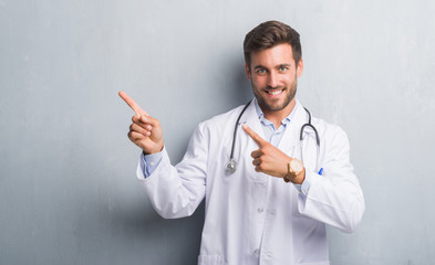 Handsome young doctor man over grey grunge wall smiling and looking at the camera pointing with two hands and fingers to the side.