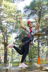 Girl in mountaineering training. She's walking on the rope. She's very happy.