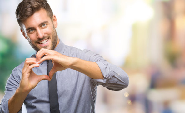 Young handsome business man over isolated background smiling in love showing heart symbol and shape with hands. Romantic concept.