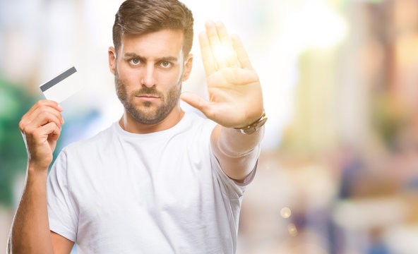 Young handsome man holding credit card over isolated background with open hand doing stop sign with serious and confident expression, defense gesture