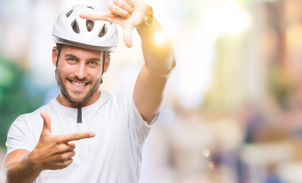 Young handsome man wearing cyclist safety helmet over isolated background smiling making frame with hands and fingers with happy face. Creativity and photography concept.