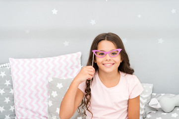 Slumber party photo booth props. Kid girl cheerful posing with retro pink eyeglasses party attribute. Prepare photo booth props hand made or buy for party. Printable photo booth props pajama party