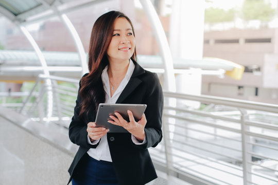 Successful asian senior businesswoman using digital tablet standing over modern office background