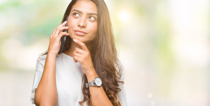 Young beautiful arab woman talking on the phone over isolated background serious face thinking about question, very confused idea