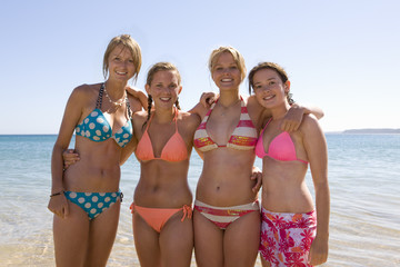 Teenage girls in bikinis by ocean on summer beach vacation at camera