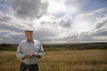 Mature farmer standing in farm field checking wheat crop at camera
