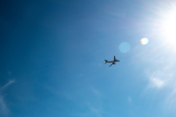passenger airplane taking off into the sun