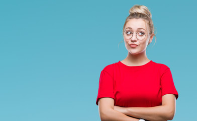 Young blonde woman wearing glasses over isolated background smiling looking side and staring away thinking.