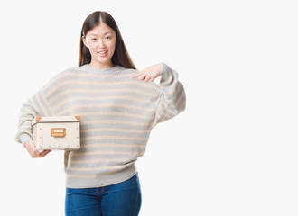 Young Chinese woman over isolated background holding a box with surprise face pointing finger to himself