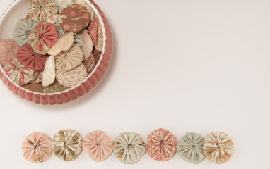 Background fabric sewing yoyos in peach and green