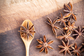 Anise star on wooden spoon and table, herb and spice, food ingredient